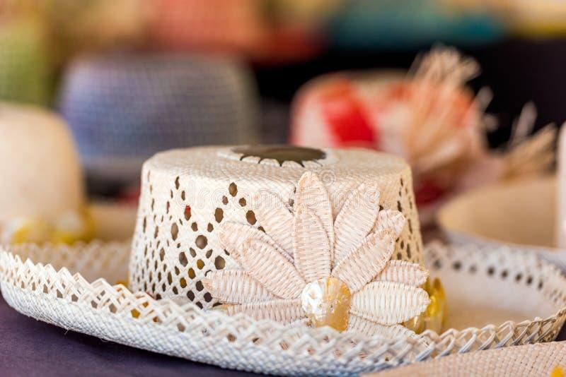Sugrörhattar som är till salu i en tropisk souvenir, shoppar i Aitutaki, kocken Islands utomhus skjutit selektivt f?r fokus arkivbilder