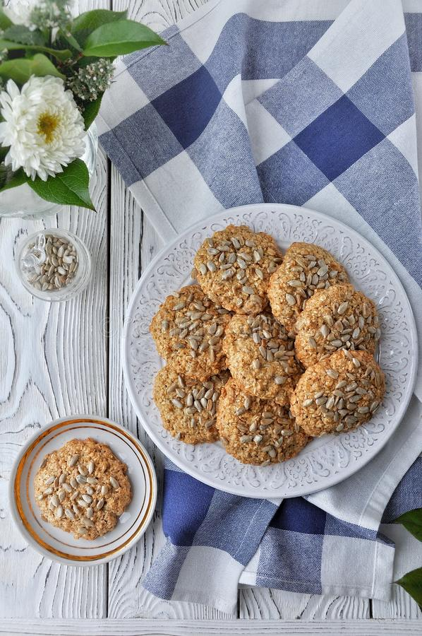 Sui biscotti di farina d'avena del piatto con i semi, fondo di legno della luce bianca Vista da sopra immagine stock libera da diritti