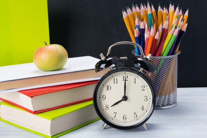 Sui libri di tavola per l'apprendimento, su uno spuntino leggero Apple e sulla sveglia fotografia stock libera da diritti