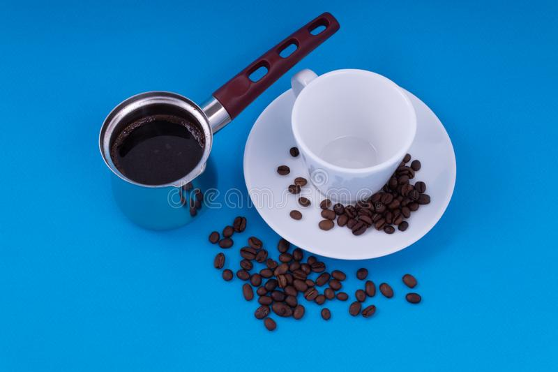 Sui precedenti blu è una tazza vuota con un piattino a sinistra della nave con caffè di recente preparato fotografie stock