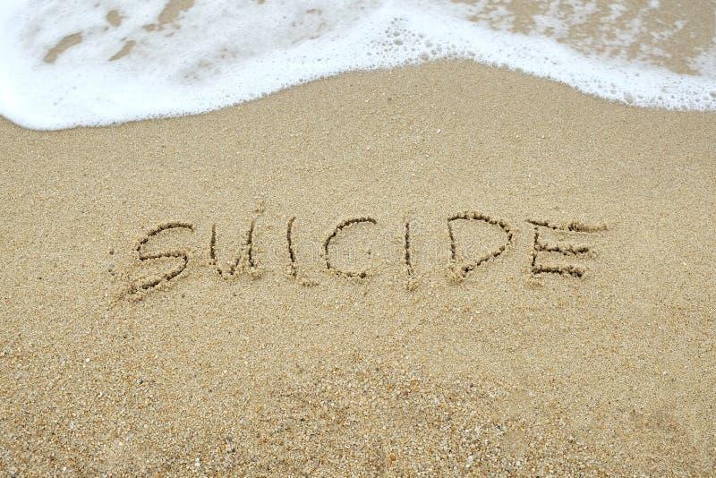 SUICIDE écrit sur le sable images stock