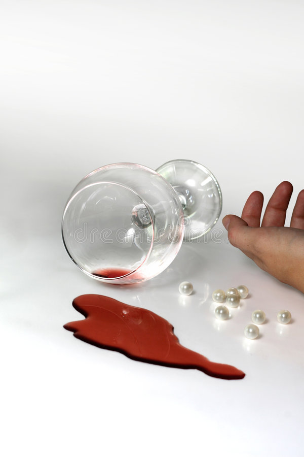Suicide. A conceptual image showing a person's hand, knocked off glass of wine and some pills royalty free stock image