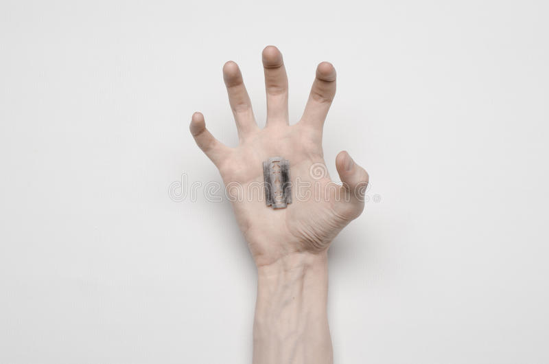 Suicide and Halloween theme: the human hand holding the blade to suicide isolated on white background in studio top view stock image