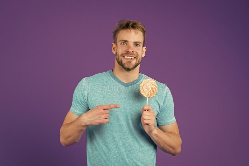 Suiker schadelijk voor gezondheid Van het de lollysuikergoed van de kerelgreep de violette achtergrond Eet de mensen knappe macho stock fotografie