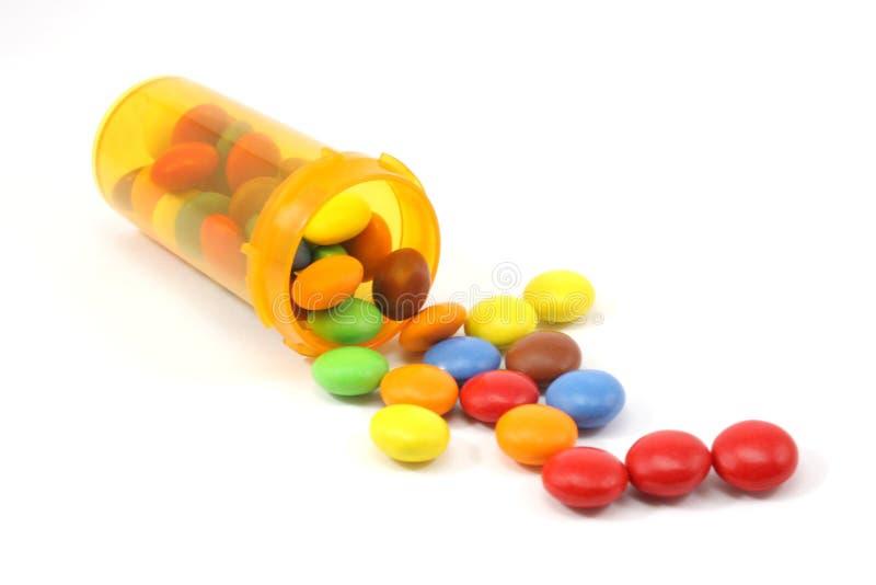 Suikergoed dat uit pillenfles morst royalty-vrije stock fotografie
