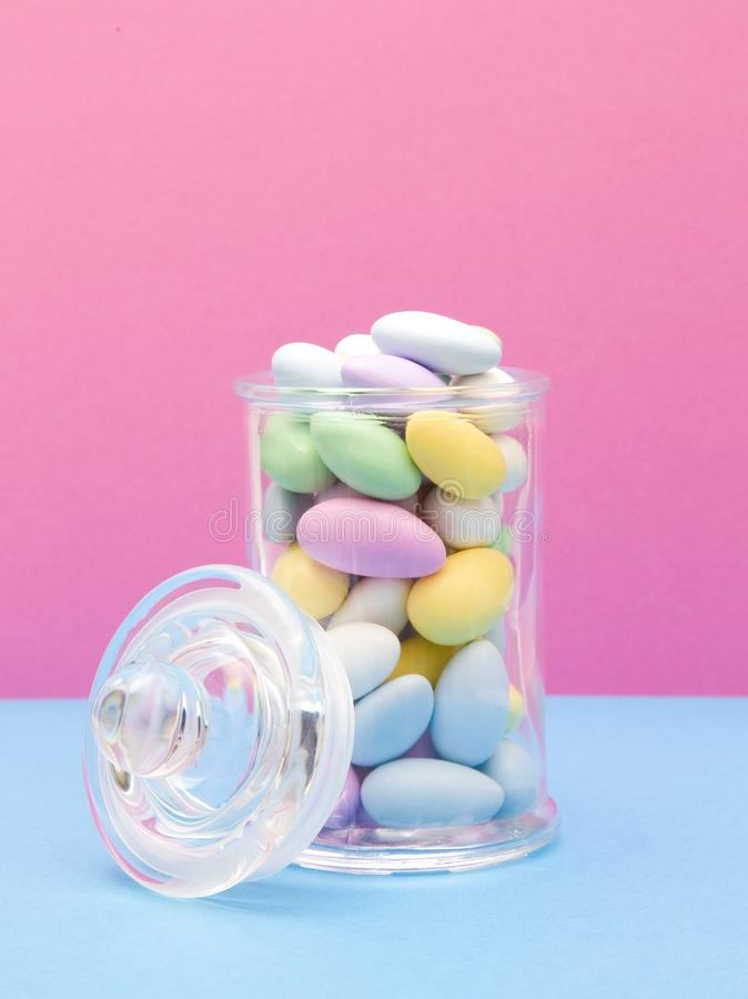 Suikergoed Met een laag bedekte Amandelen op een Roze en Blauwe Achtergrond stock foto