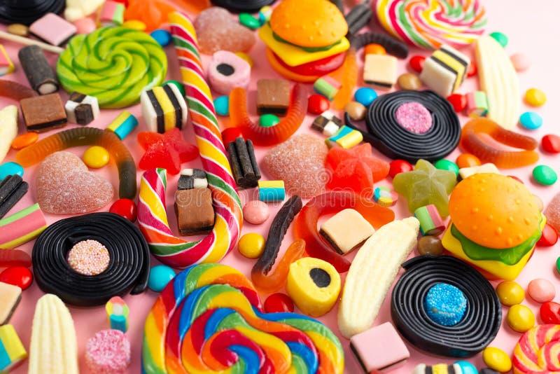 Suikergoed met gelei kleurrijke serie van verschillende childssnoepjes en traktaties over roze zoals feestelijke achtergrond royalty-vrije stock foto's