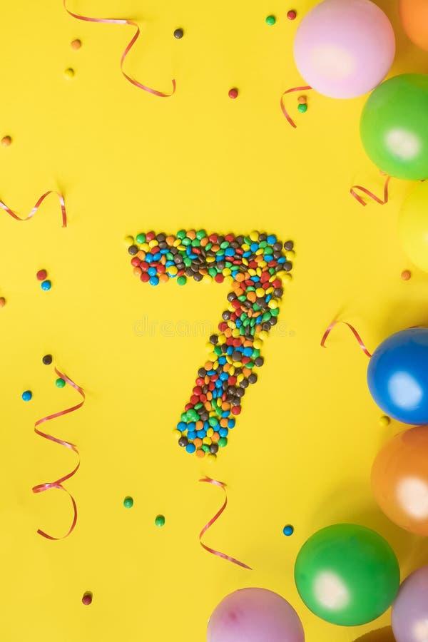 Suikergoed nummer 7 met kleurrijke ballons op gele achtergrond Concept voor verjaardagen stock foto's