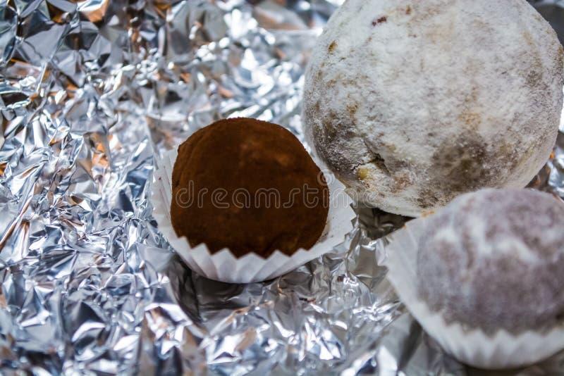 Suikergoed, smakelijk van natuurlijke chocolade, in de vorm van een bal Een hulpachtergrond van een folie Spel van licht en flard royalty-vrije stock foto