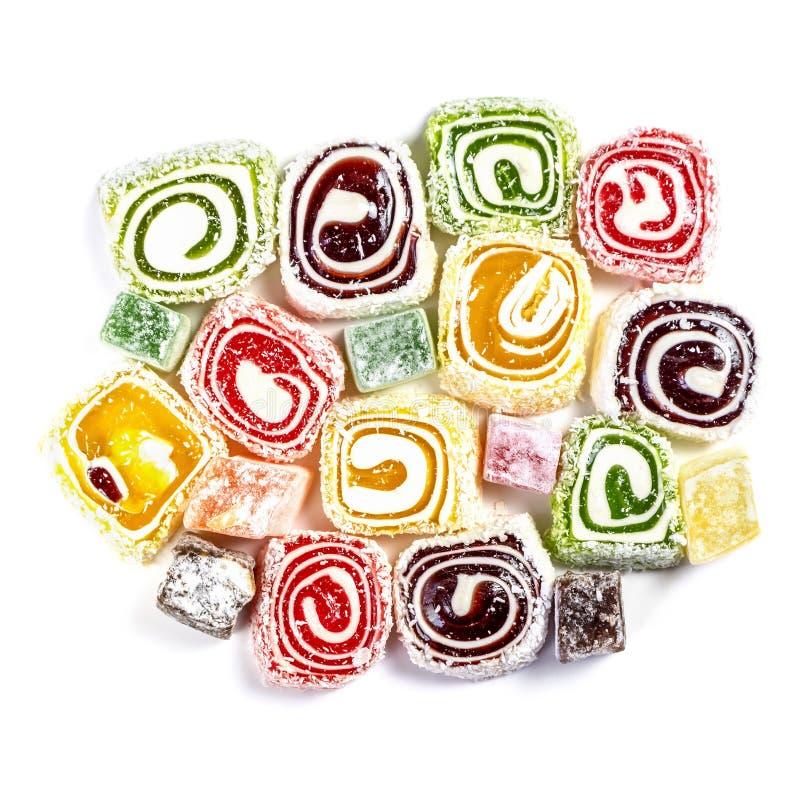 Suikergoedachtergrond op witte achtergrond wordt geïsoleerd die Gekleurd die suikergoed in een broodje wordt en met kokosnotenvlo stock fotografie