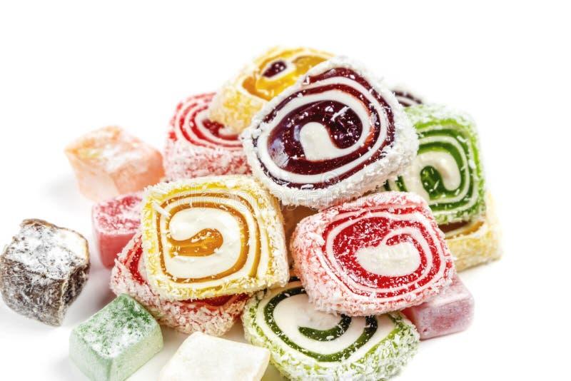 Suikergoedachtergrond op witte achtergrond wordt geïsoleerd die Gekleurd die suikergoed in een broodje wordt en met kokosnotenvlo royalty-vrije stock afbeelding