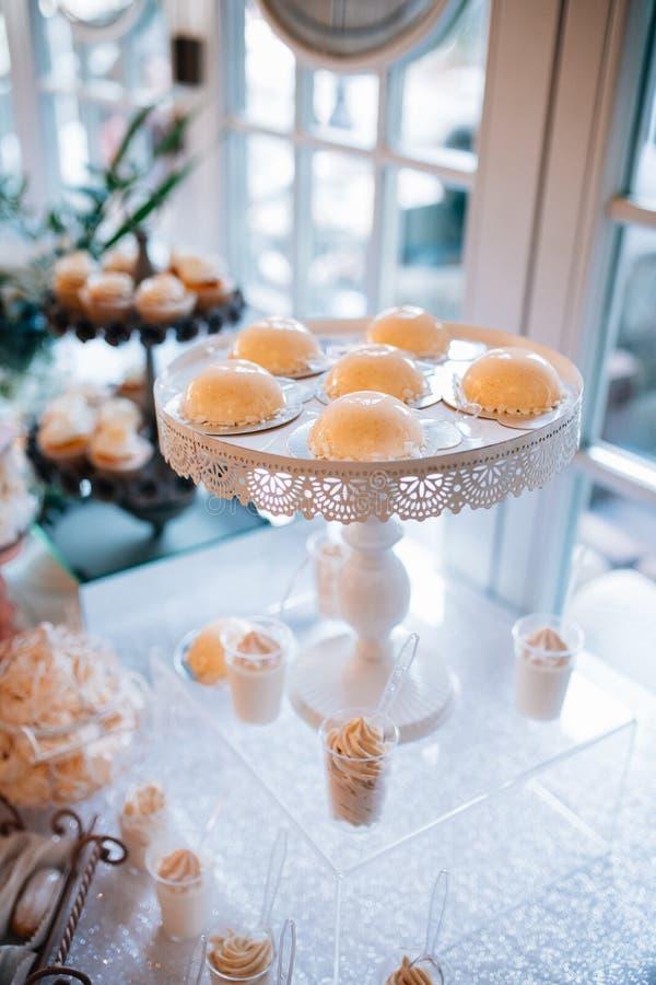 Suikergoedbar en huwelijkscake met bloemen Lijst met snoepjes, buffet met cupcakes, suikergoed, dessert royalty-vrije stock foto