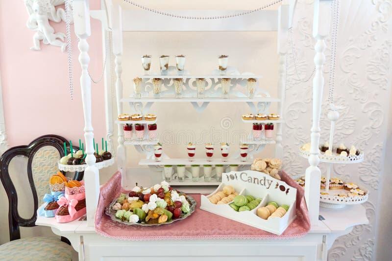 Suikergoedbar op de lijst met snoepjes, vruchten, makarons en andere desserts royalty-vrije stock afbeelding