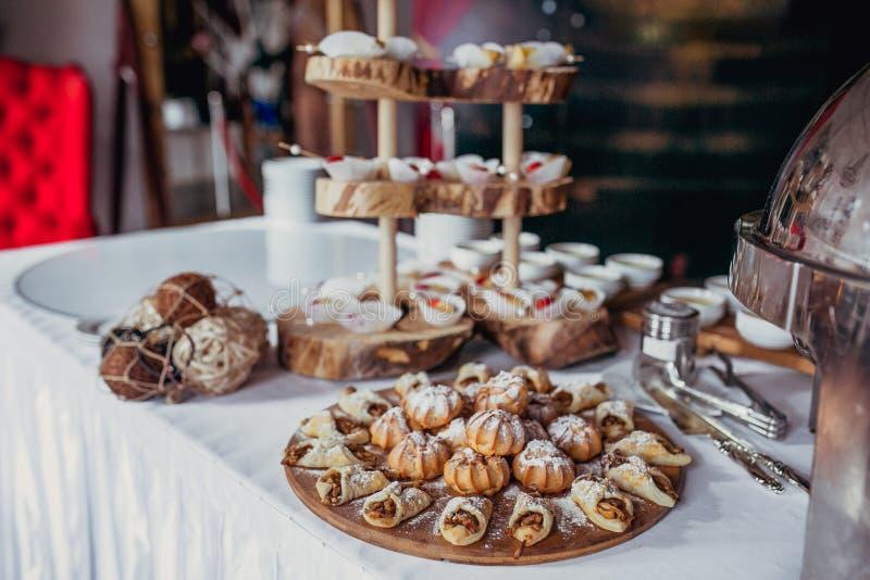 Suikergoedbar op verjaardagspartij met heel wat verschillende suikergoed, cupcakes, soufflé en cakes Verfraaid op houten tribunes stock foto's
