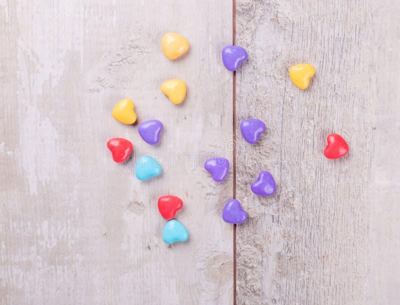 Suikergoedharten over hout De achtergrond van de valentijnskaartendag stock afbeeldingen