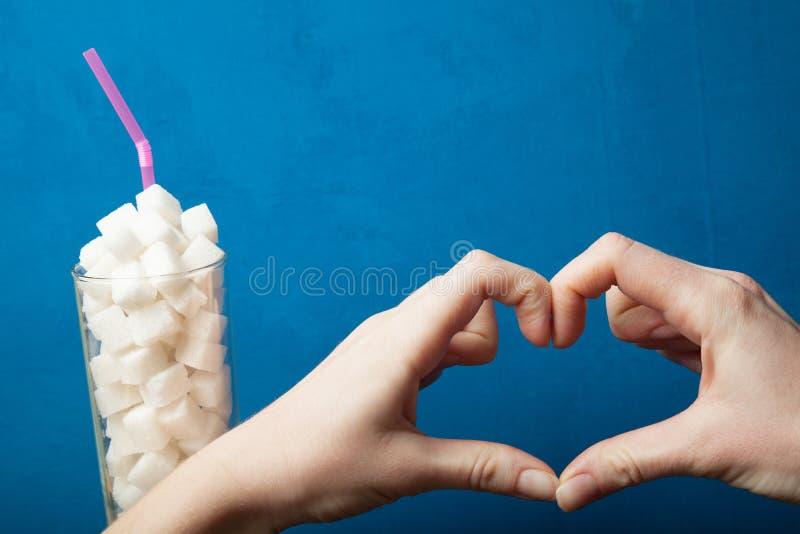 Suikerverslaving, hartteken en suiker op een blauwe achtergrond royalty-vrije stock afbeeldingen