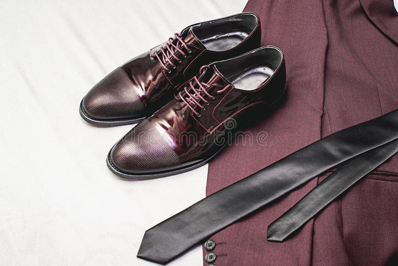 Suit, necktie, leather shoes on a white textile. Grooms wedding morning. Close up of modern man accessories. Look from above royalty free stock images