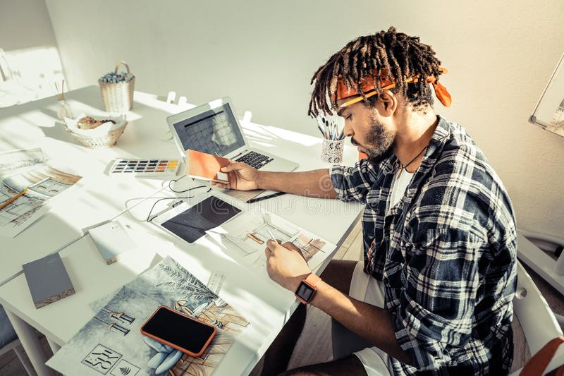 Bearded interior artist choosing suitable colors for his new project. Suitable colors. Bearded professional interior artist choosing suitable colors for his new stock images