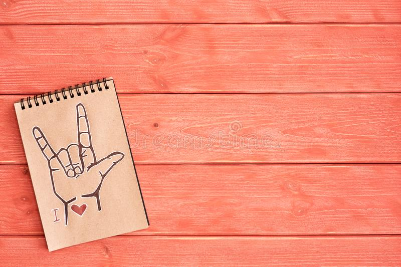 A notebook of Kraft paper with a painted symbol ASL American Sign Language ILY I Love you that lies on the textured wooden royalty free stock photo