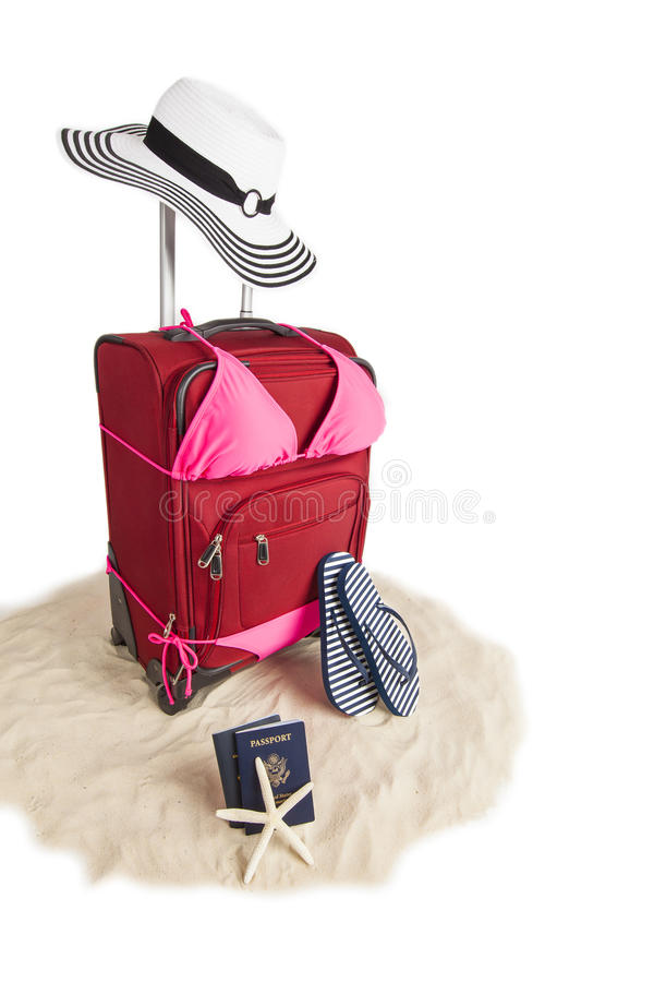 Suitcase In Bikini Ready For A Beach Vacation. Picture of Red Suitcase In Bikini Bathing Suit Ready for Travel To Beach Vacation With Sandals, Sand, Beach Hat royalty free stock photos