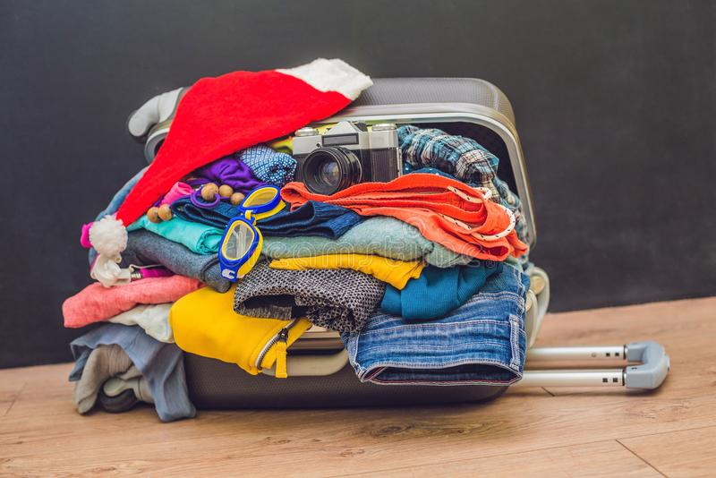 a suitcase with clothes and a Christmas hat. Journey to Christmas. royalty free stock photo