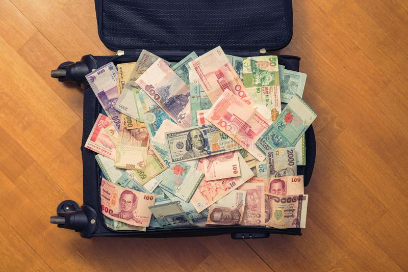 Suitcase full money of south-east Asia and American hundred dollar bill. Currency of Hong Kong, Indonesia, Malaysia, Thai, Singapo. Re dollar. Travel royalty free stock photos