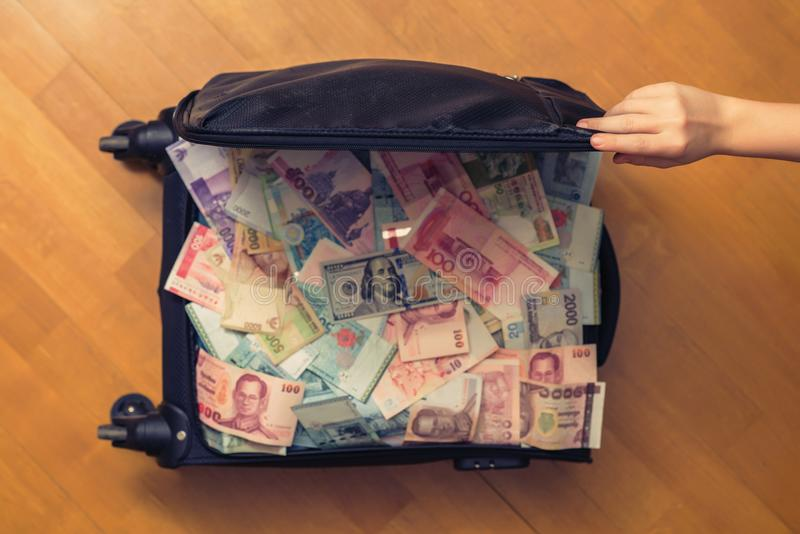 Suitcase full money of south-east Asia and American hundred dollar bill. Currency of Hong Kong, Indonesia, Malaysia, Thai, Singapo. Re dollar. Travel royalty free stock photography
