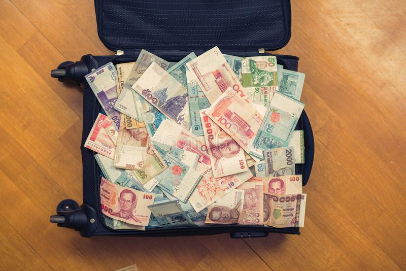 Suitcase full money of south-east Asia. Currency of Hong Kong, Indonesia, Malaysia, Thai, Singapo. Re dollar. Travel stock photos