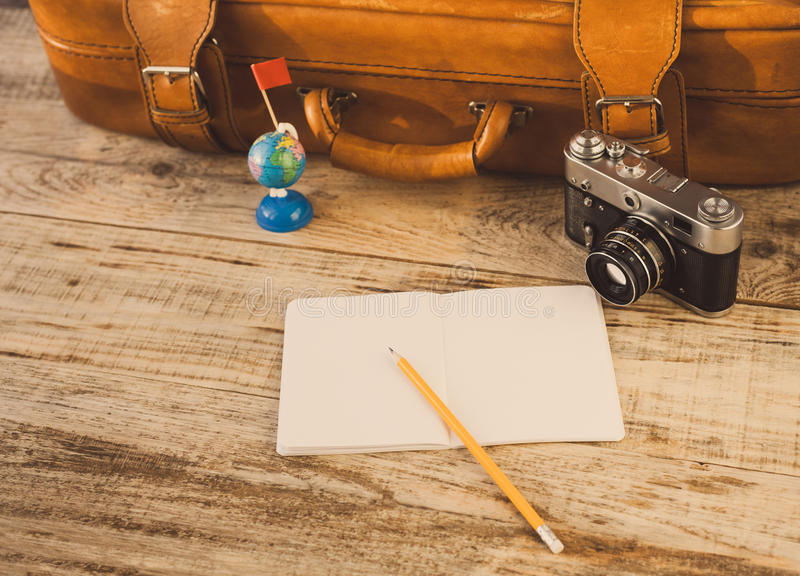 Suitcase, nootbook, pencil, flag, vintage camera on wooden planks. Aim, attainment, target, tourism, travel. At dawn. Hipster styl. Old Suitcase, nootbook stock photography