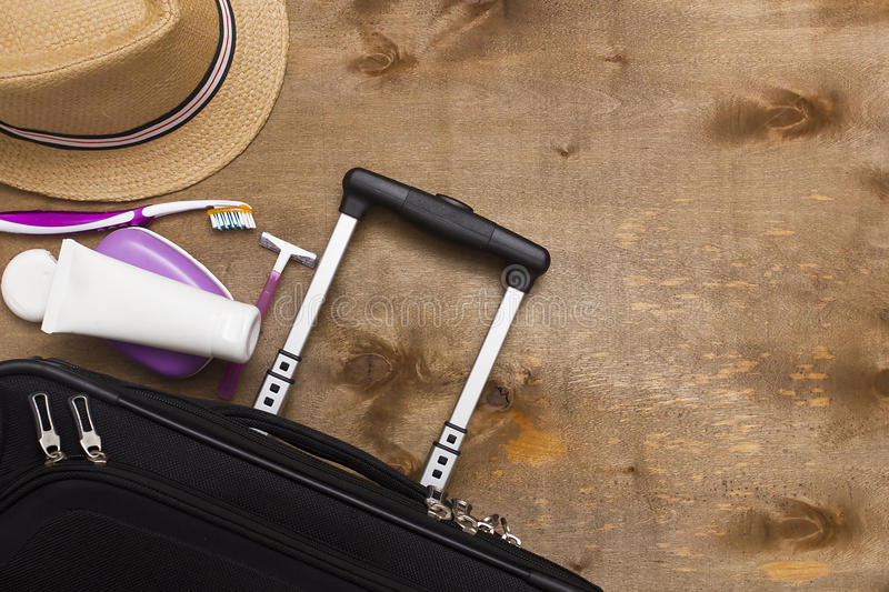 Suitcase traveler and toiletries. Suitcase traveler, toiletries and a hat on a wooden background royalty free stock image