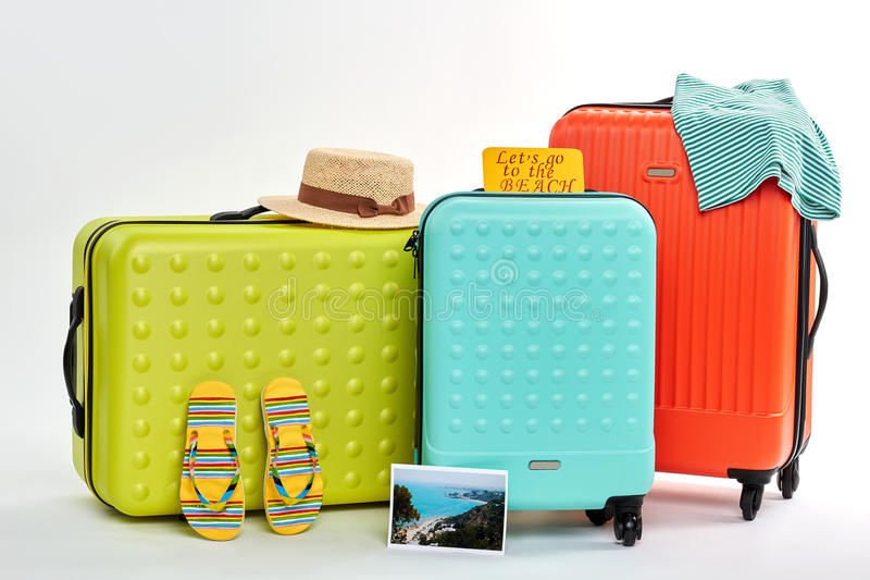 Suitcases, clothes, seaside photo. Image of coast near summer accessories. Time to go on beach royalty free stock photos
