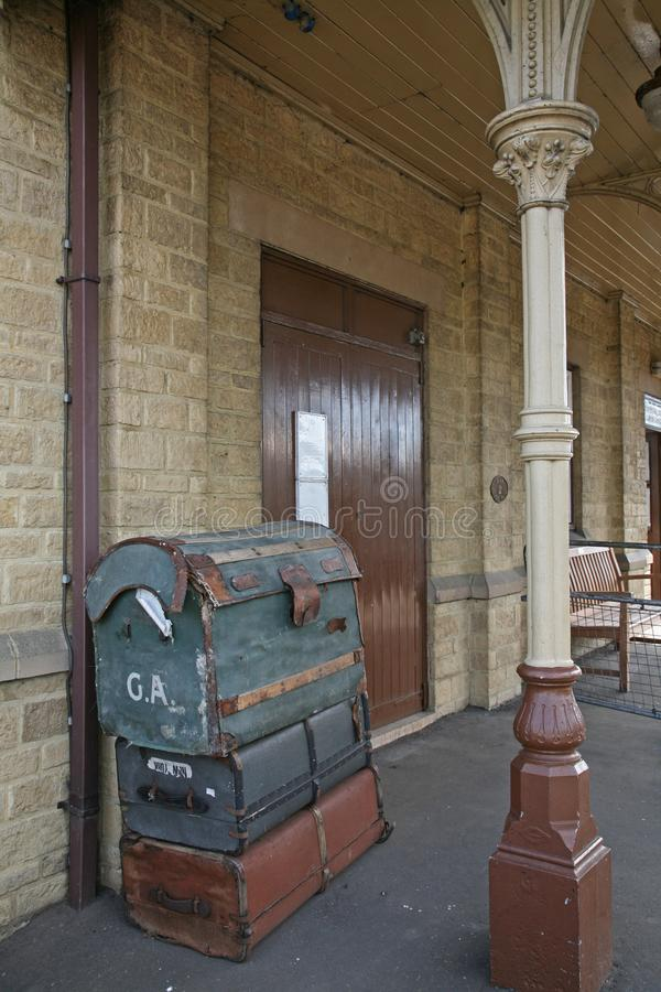 Suitcases stacked in an old railway station. Suitcases stacked on the platform in an old Victorian railway station in the UK stock photo