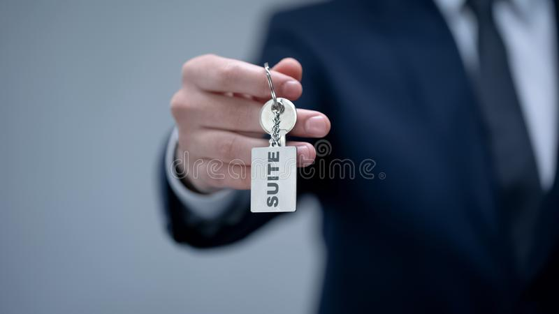 Suite word on keychain in businessman hand, rental premium quality accommodation stock photography