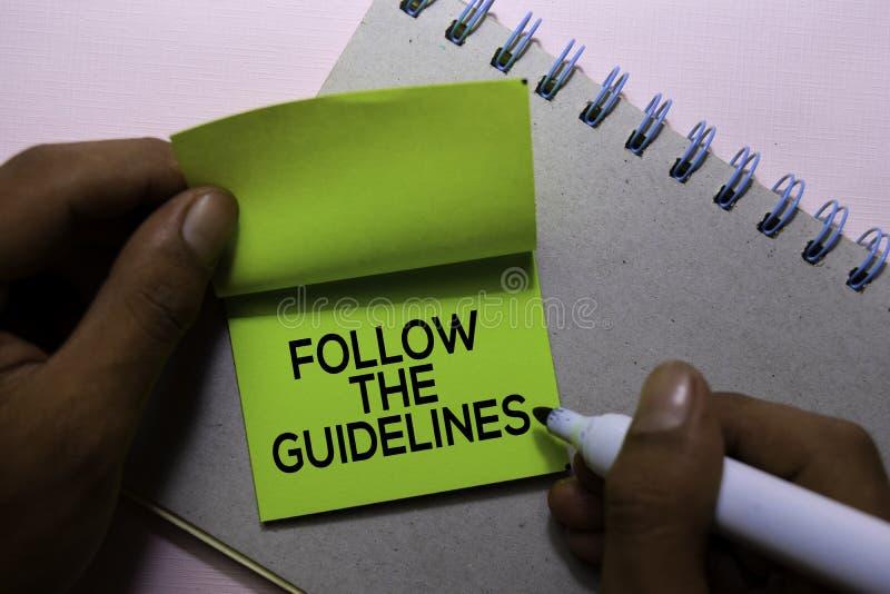 Suivez les directives textotent sur les notes collantes d'isolement sur le bureau photo libre de droits