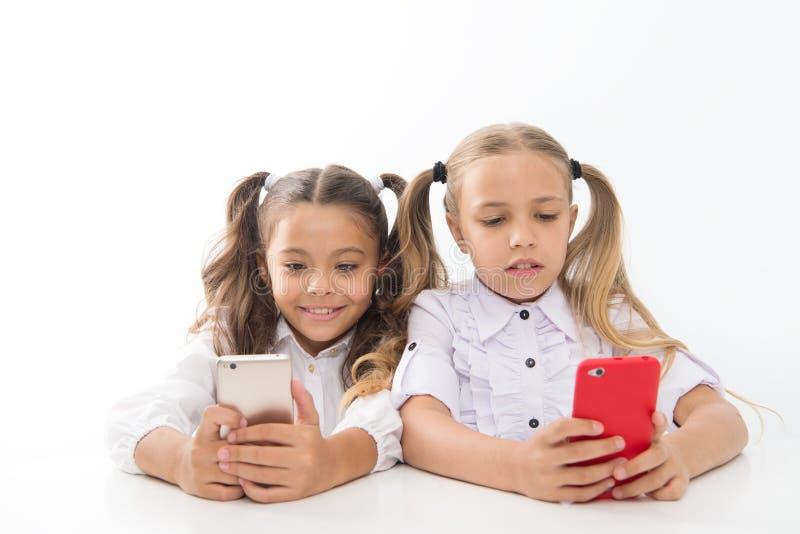 Suivez les réseaux sociaux Jeu en ligne École de Blogger application ?ducative Smartphones d'écolières surfant l'Internet photos stock