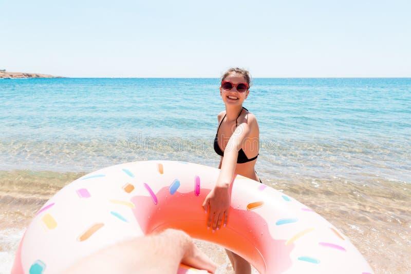 Suivez-moi concept de vacances les girlcalls ? nager en mer et ondule sa main Fille d?tendant sur l'anneau gonflable en mer ?t? images stock