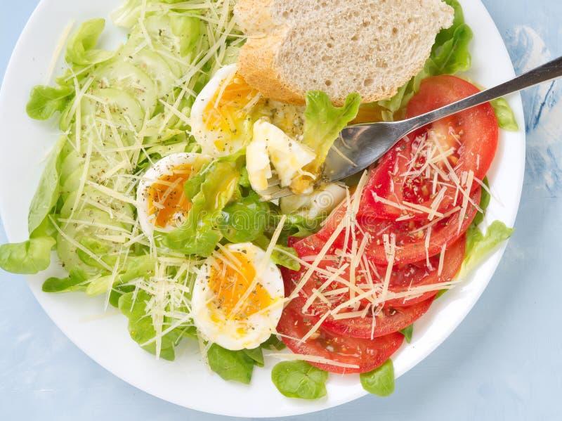 Suivez un régime la salade avec les oeufs à la coque, le fromage et les légumes mous - tomates, laitue Fond clair bleu, fin de vu photo libre de droits