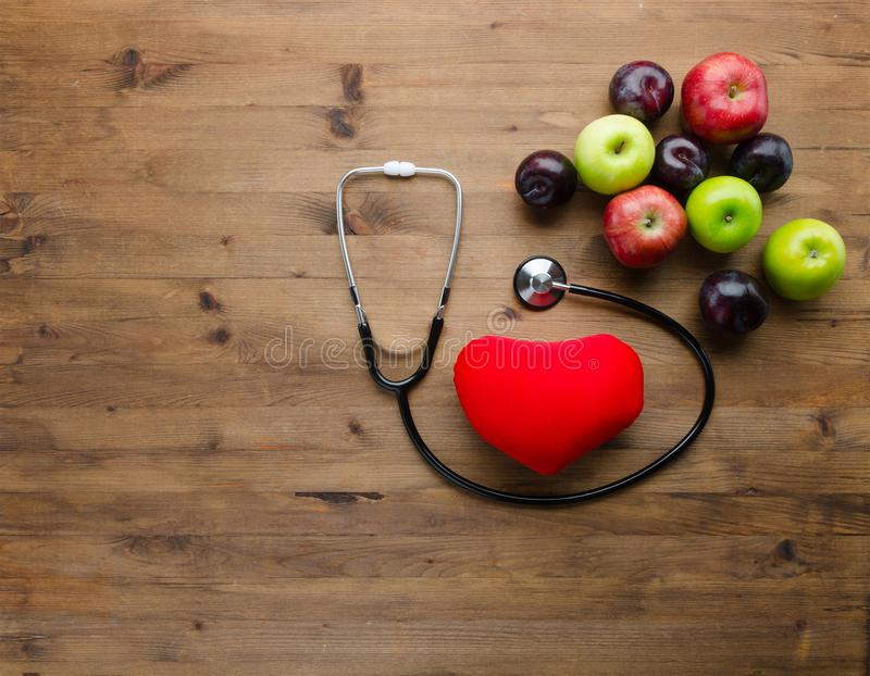 Suivez un régime le concept avec le jouet et les fruits frais médicaux de coeur de stéthoscope images stock