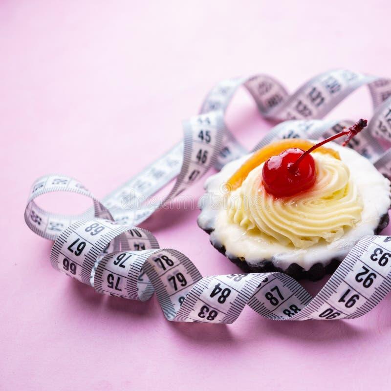 Suivez un régime le concept petit gâteau et bande doux de mesure photographie stock