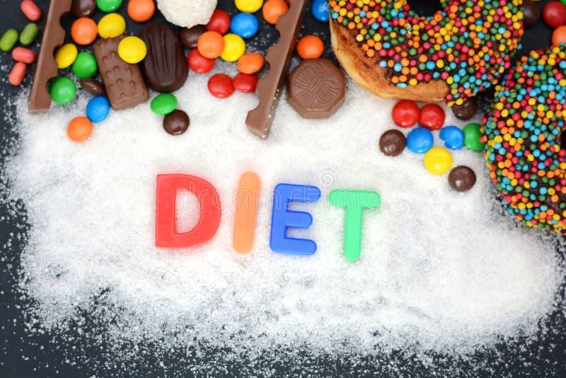 Suivez un régime le mot écrit sur la poudre de sucre blanc avec de divers bonbons photographie stock