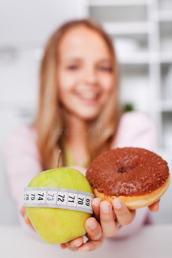 Suivez un régime les choix d'une jeune fille - pomme ou beignet photos stock