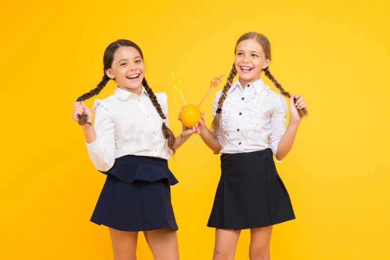 Suivre un régime d'école Élèves d'école primaire buvant du jus des fruits oranges sur le fond jaune Petit apprécier d'enfants photographie stock libre de droits