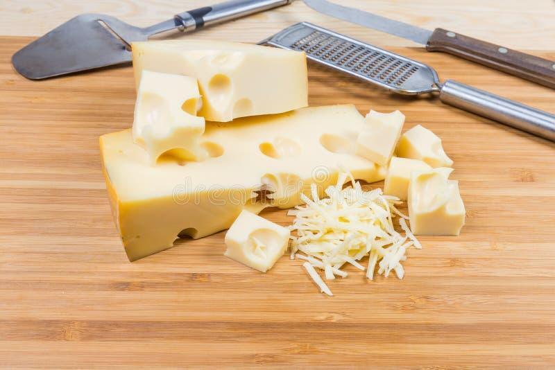 Suizo-tipo en parte cortado y rallado queso en tabla de cortar fotografía de archivo libre de regalías