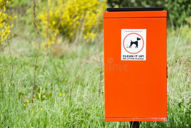 Sujar do cão escolhe-o acima do sinal no escaninho vermelho imagens de stock