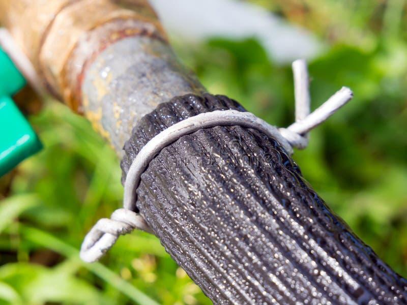 Sujeción de la manguera al tubo con una abrazadera de alambre imagen de archivo
