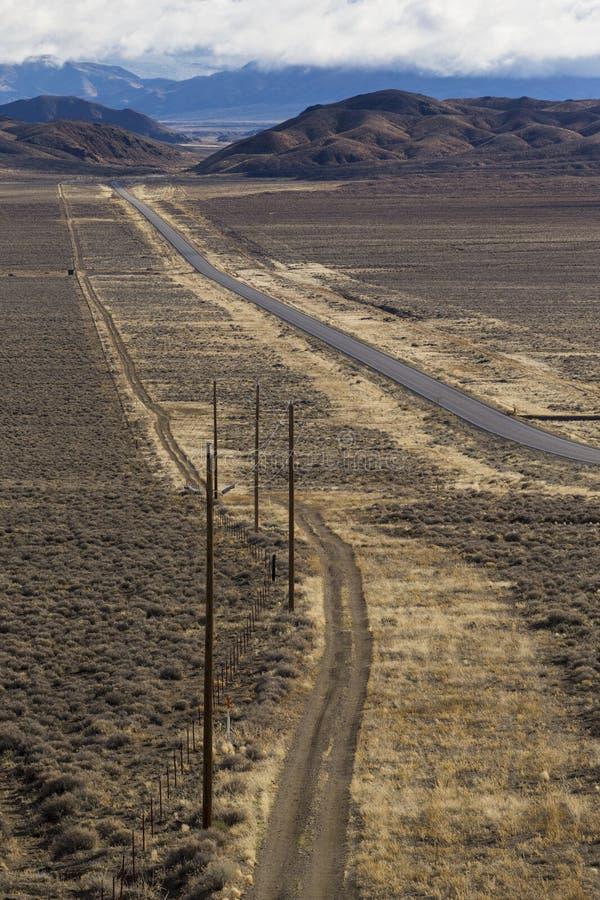 Sujeira e estrada pavimentada no deserto de Nevada sob o céu azul com nuvens imagens de stock