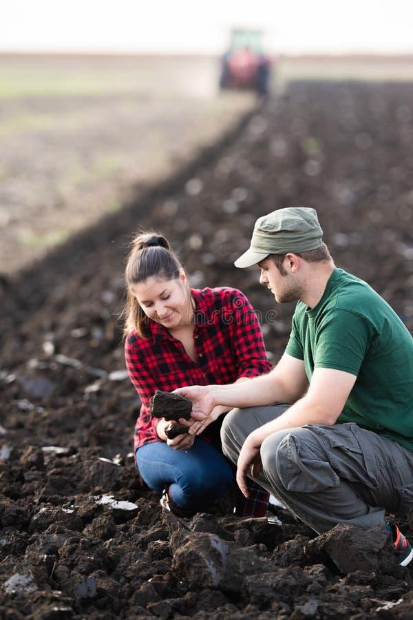 Sujeira nova do exame dos fazendeiros quando o trator arar o campo imagens de stock royalty free