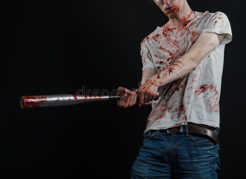 Sujet ensanglanté : Le type dans un T-shirt ensanglanté tenant une batte ensanglantée sur un fond noir photographie stock