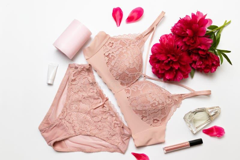 Sujetador rosado elegante femenino del cordón, peonía plana, barra de labios, crema y pasador en un fondo blanco, endecha plana d foto de archivo libre de regalías