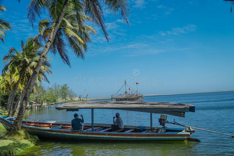 Sukabumi, West Java, Indonesia, September 7th 2018 : The men were talking on a boat that was leaning by the beach. Scenic, thailand, wild, dawn, sunset royalty free stock image
